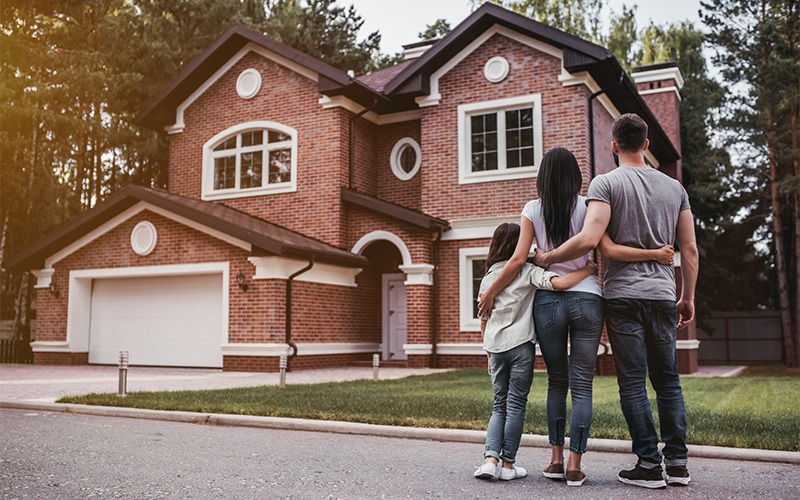 Family standing outside a modern brick home
