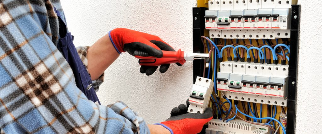 Man wearing gloves setting up an electrical system